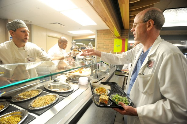 Executive Chef Ryan Kendall, left, hands a plate of food to Dr. Eric Weatley on the opening day of the St. Joe's Market Cafe at St. Joseph Mercy Hospital in Ypsilanti, Mich. on Sept. 6, 2011. Angela J. Cesere | AnnArbor.com