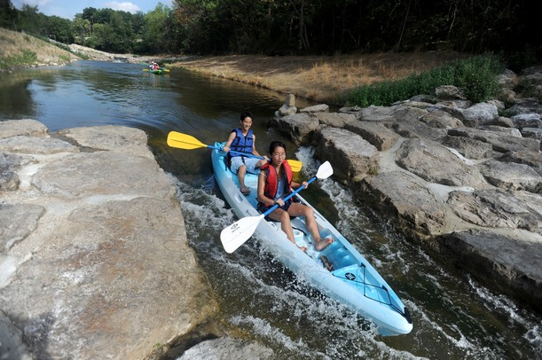 Ann Arbor residents Stephanie Huang, age 20, and her brother Daniel, age 18, take their kayak through the Argo Cascades in Ann Arbor on Saturday morning. Angela J. Cesere | AnnArbor.com
