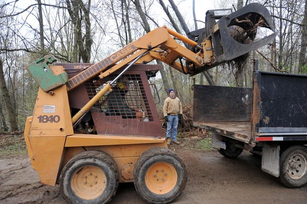 Irish Hills resident Tom Hines, left, moves heavy tree stumps and roots into a flatbed truck on the property of the Fike family. Angela J. Cesere | AnnArbor.com