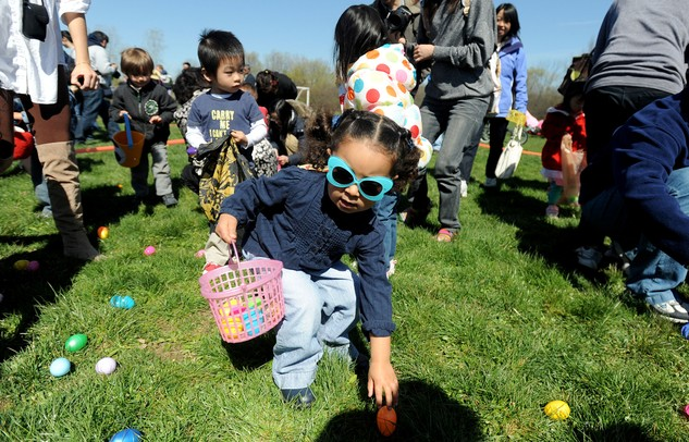 Ann Arbor resident Dalia Albashir, center, age 3, picks up a plastic egg during the egg scramble at Ann Arbor Jaycees Spring Eggstravaganza at Southeast Area Park in Pittsfield Township. Angela J. Cesere | AnnArbor.com