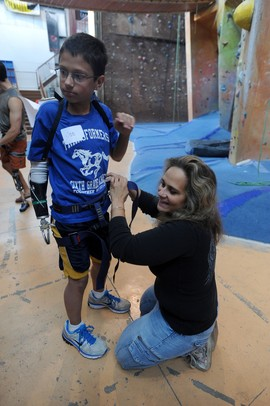 Romulus resident Michelle Bilicki, right, helps put a climbing harness on her son, Joe Bialek, age 12, for the First Climb event sponsored by the University of Michigan Orthotics and Prosthetics Center and the U-M Community Amputee Network at Planet Rock in Ann Arbor. Angela J. Cesere | AnnArbor.com