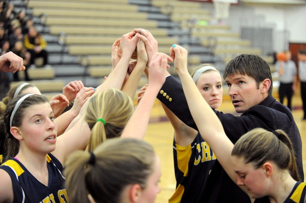 Chelsea head coach Todd Blomquist and team put their hands in to get fired up after a timeout.  Angela J. Cesere