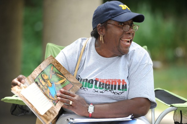 Ann Arbor resident Lauretta Flowers reads the story of Wilma Rudolph, the first American female runner to win three gold medals in the Olympics, during the 18th annual Juneteenth celebration at Wheeler Park. Juneteenth is the celebration of June 19, 1865, when Africans in Texas and the Southwest were told of the abolition of slavery and their subsequent freedom. The event features live music, games, food and other activities. Angela J. Cesere | AnnArbor.com