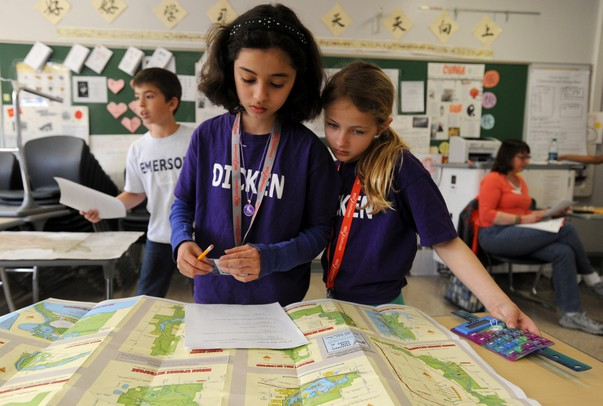 Dicken Elementary School 4th graders Sarah Akaaboune, left, and Morraina Tuzinsky, solve geographical questions with maps during the map during portion of the Washtenaw Elementary Science Olympiad at Pioneer High School Saturday afternoon. Angela J. Cesere