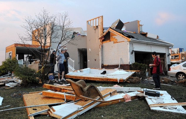 People move belongings out of a house on the corner of Meadow View and York St. in Dexter after a tornado struck their home. Angela J. Cesere | AnnArbor.com