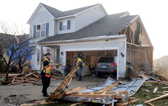 Firemen help clear debris from a yard on Noble St. in Huron Farms after a tornado hit Dexter, Mich. on March 15, 2012. Angela J. Cesere | AnnArbor.com