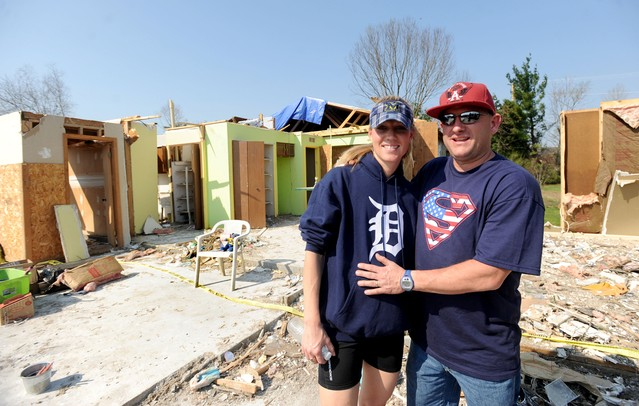Katie and Bob Jazwinski stand in front of their severely damaged home in the Carriage Hills neighborhood in Dexter. The Jazwinski family survived the tornado by hiding in a closet inside a bedroom of the house. Angela J. Cesere | AnnArbor.com