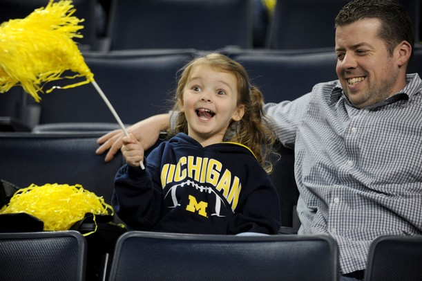 Toledo resident Bill LaGrange, right, watches his 4-year-old daughter Carli cheer during the basketball game. Angela J. Cesere | AnnArbor.com