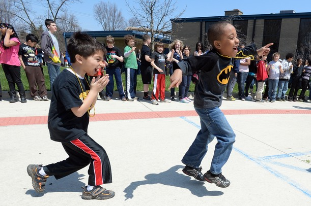Carpenter Elementary school first graders Sabeeh Shaw and Christian Brown dance to the beat of the Huron High School drumline as they march around the school for a 175th birthday celebration on Friday, April 26, 2013. Melanie Maxwell I AnnArbor.com