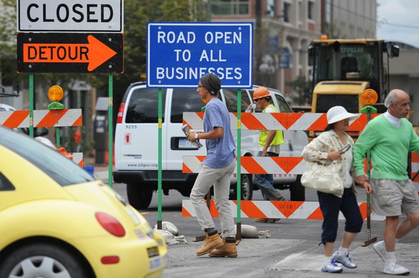 Pedestrians walk past signs as construction continues along Fourth Avenue between East Huron and Liberty streets in downtown Ann Arbor on Monday, July 29, 2013. Melanie Maxwell | AnnArbor.com