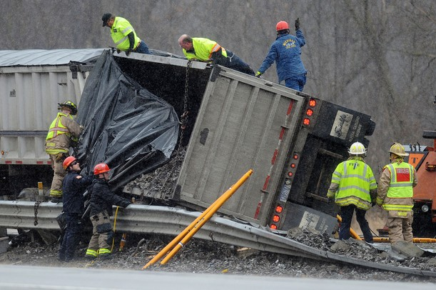 Rescue crews work to secure chains to a turned over trailer as they prepare to lift it upright using two tow trucks. The trailer flipped onto its side, spilling part of its load and pinning another vehicle against the guardrails on south U.S. 23 north of Six Mile Road in Northfield Township on Monday, March 11, 2013. Melanie Maxwell I AnnArbor.com