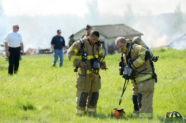 Firefighters strap on their gear during a training exercise and controlled burn in 6700 block of Warner Rd. in Pittsfield Township on Thursday, May 9, 2013. Melanie Maxwell I AnnArbor.com
