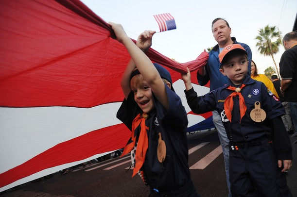 Young Boy Scouts help carry a large American flag during the Outback Bowl New Year's eve parade in Ybor City, Fla. on Monday night. Melanie Maxwell I AnnArbor.com