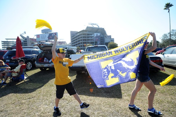 Michigan fans Kaden Churchill, 10, of Fla., and his cousin Abby Cribley, 14, of Jenison, march a Michigan flag through their tailgating section outside of Raymond James Stadium before the start of the Outback Bowl in Tampa, Fla. on Tuesday, Jan. 1. Melanie Maxwell I AnnArbor.com