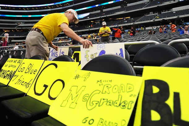 Michigan fan Gary Myers, of Denver, Colorado, distributes the signs he made over two rows of seats before the start of Michigan's Elite Eight game against Florida at Cowboys Stadium on Sunday, March 31, 2013. Melanie Maxwell I AnnArbor.com