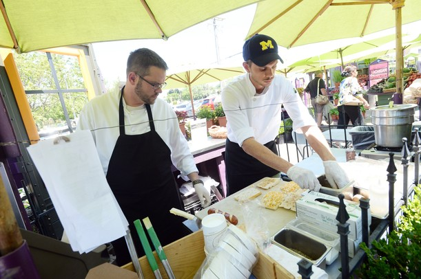 Chef Steven Grostick and grill chef Doug Perkins work outside at the grill during lunch at the Produce Station on Thursday afternoon. Melanie Maxwell | AnnArbor.com