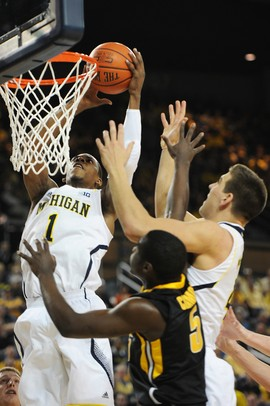 Michigan freshman Glenn Robinson III takes the ball to the hoop over freshman Mitch McGary and Iowa freshman Anthony Clemmons during the first half against Iowa at Crisler Center on Sunday, Jan. 6. Michigan beat Iowa 95-67 in the Big Ten home opener. Melanie Maxwell I AnnArbor.com