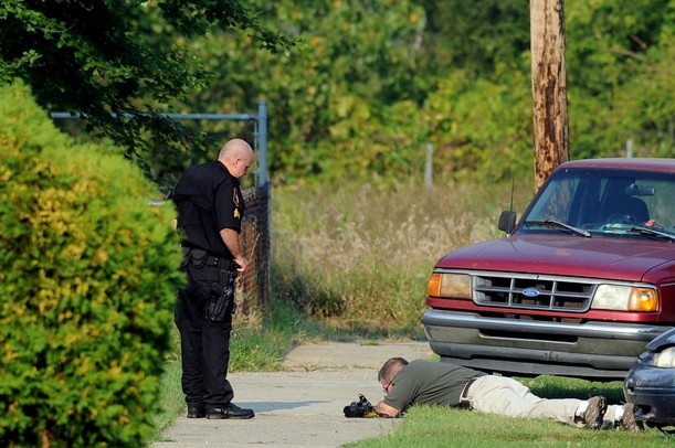 A Washtenaw County Sheriff investigator inspects something on the ground as a deputy looks on in front of a home on Tyler Rd. on Wednesday, August 21, 2013. Melanie Maxwell | AnnArbor.com