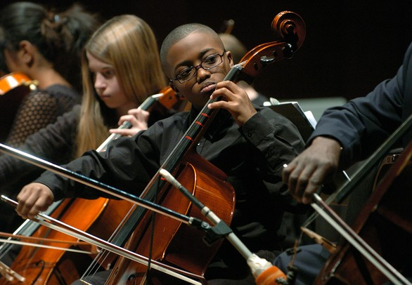 Scarlett Middle School eighth-grade cellist James Andrews, center, looks to director Mitchell Lawrence during Orchestra Night, which featured all five Ann Arbor middle school concert orchestras, along with performances from the Huron and Pioneer high school symphony orchestras.