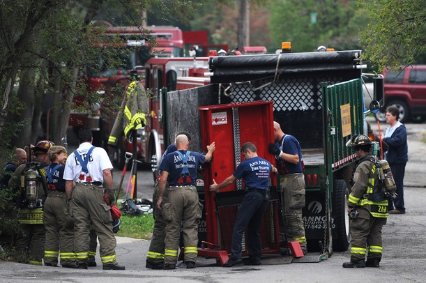 Ann Arbor firefighters navigate an 1100-pound door from a truck as they set up obstacles for training at Parkhurst Apartments on Wednesday morning. The complex is scheduled to be demolished and offers a good training ground for the firefighters.  Melanie Maxwell I AnnArbor.com