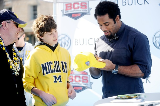 Michigan fans Vito Peraino and his son Dominick, 14, both of Cincinnati, meet with former Michigan football player Dhani Jones as he signs autographs during the Allstate Fan Fest in New Orleans, LA, on Monday.  Melanie Maxwell I AnnArbor.com
