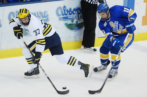 Michigan sophomore Mac Bennett looks to move the puck around Lake Superior State sophomore Colin Campbell in the first period at Yost Arena on Friday night. Melanie Maxwell I AnnArbor.com