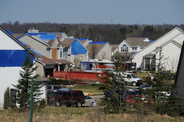 Blue tarps cover several rooftops Monday as crews work to salvage and clean up tornado-damaged homes in the Huron Farms subdivision in Dexter. Melanie Maxwell I AnnArbor.com