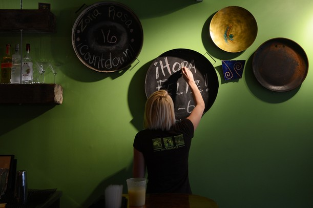 Isalita bartender Billi Bowman freshens up a chalkboard near the bar.  Melanie Maxwell I AnnArbor.com