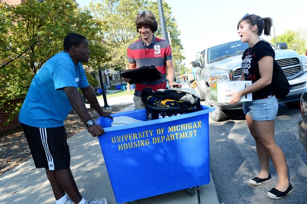University of Michigan freshman and Move-In-Maker DeAnthony Hardison, of Detroit, left, helps incoming freshman Adam Spanske, of Romeo, with his belongings as Spanske's sister Amy stands by during move in at Couzens Hall on Wednesday morning.  Melanie Maxwell I AnnArbor.com