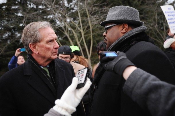 Governor Snyder's chief of staff Dennis Muchmore, left, listens to Rev. Charles Williams II, of Detroit, during a Jan. 16 rally outside of the governor's subdivision in Ann Arbor. Protesters were opposing the state's emergency manager law. Melanie Maxwell I AnnArbor.com