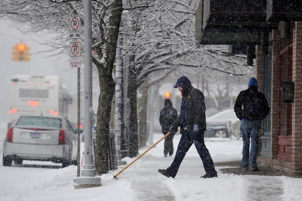 A man shovels the sidewalk in front of several businesses along W. Washington near S. State street on Tuesday morning.  Melanie Maxwell I AnnArbor.com