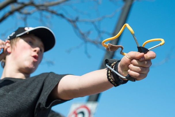 "Gavin Lemieus of Ann Arbor fires off a ""seed bomb"" at the Water Street property in Ypsilanti using a slingshot, Wednesday, May 1.