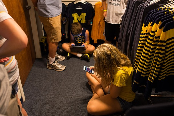 Kids play on their iPads and iPhones as they wait for former Wolverines basketball players Trey Burke, Tim Hardaway Jr, and Josh Bartelstein to sign autographs at the MDen in Ann Arbor, Saturday, August, 24.