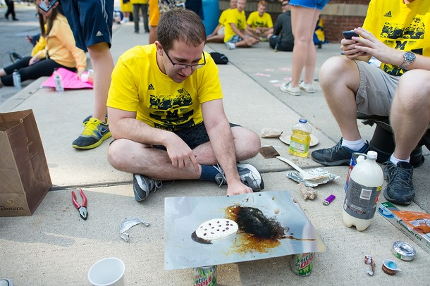 Ethan Stark, a first year Ph.D. student, cooks up pancakes using a makeshift stove as he waits in line for the Michigan  student section queue to open.