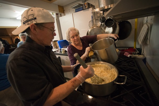 Volunteers John Gary and Sandy Yarbrough make mashed potatoes in the Vineyard Church kitchen.