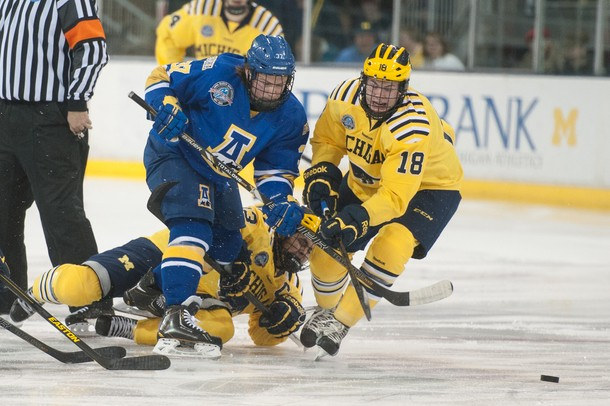 The Wolverines left wing Andrew Copp and the Nanooks Cody Kunyk race towards the puck after the face-off, Saturday Jan. 12.