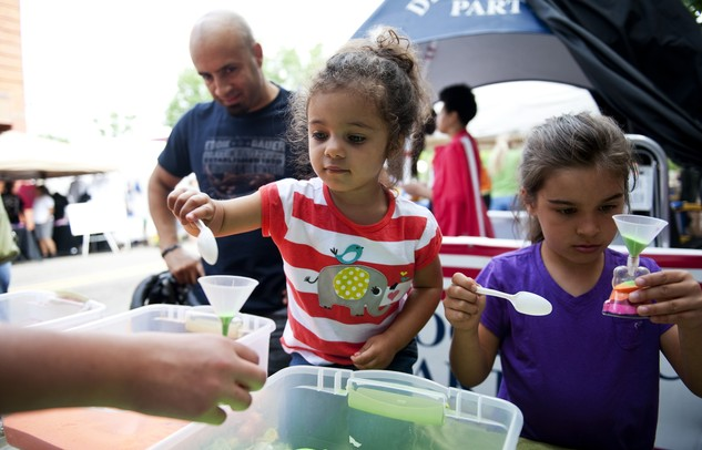 Gabriella Porter, 2, and Maya Miller, 7, create sand dart necklaces at the James Lee Family and Cosmetic Dentistry tent during the 18th annual African American Downtown Festival on Saturday, June 1. Daniel Brenner I AnnArbor.com