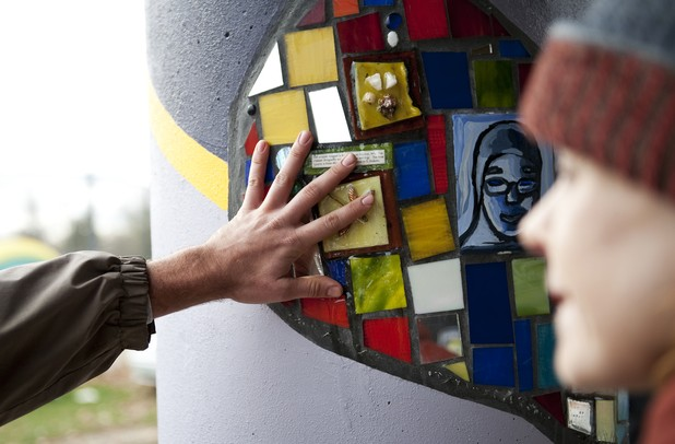 Aaron Hammer feels the mosaic mural at Allmendinger Park on Sunday. Hammer lives across the street and appreciates the public artwork and thinks it connects the community. Daniel Brenner I AnnArbor.com
