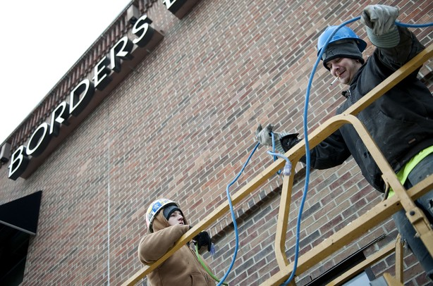 Foreman Shaun Michaels and Laborer Zach Dillinger organize extension cords on top of a scissor lift before removing the Borders sign on Liberty Street on Monday Dec. 31. Daniel Brenner I AnnArbor.com