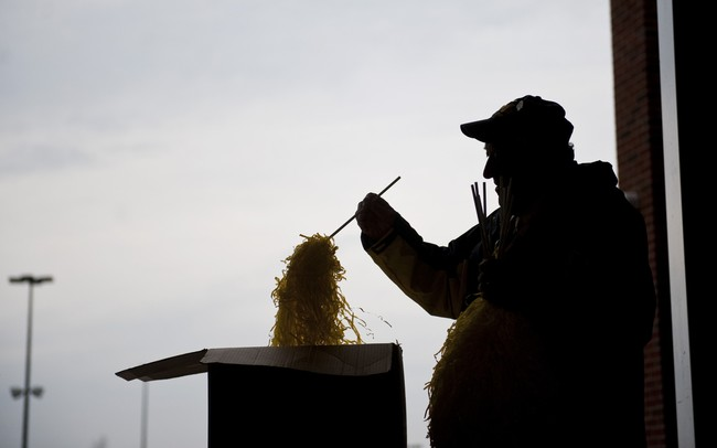 Michigan basketball usher James Prokos sorts and distributes pom poms near an entrance to Crisler Arena before the welcome home party on Tuesday, April 9. AnnArbor.com I Daniel Brenner