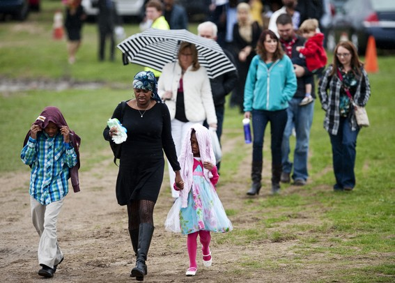 Family and friends walk through rain from the paring lot to the Convocation Center for the Eastern Michigan University Spring Commencement on Sunday, April 28. Daniel Brenner I AnnArbor.com