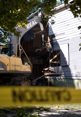 An excavator begins to tear apart a house at the intersection of Kingsley Street and First Street on Monday morning. Daniel Brenner I AnnArbor.com
