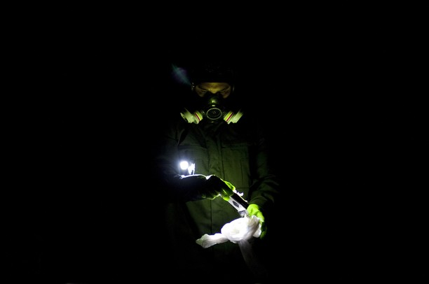 A member of the Michigan State Police Meth Response Team collects evidence and neutralizes hazardous material removed from a Ford Mustang on Briarbrook Drive in Ypsilanti on Monday. They were alerted after a man was found making meth in the front seat of the car. Daniel Brenner I AnnArbor.com