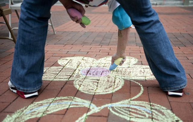 "Lynnie B uses chalk to draw artwork in the diag of Michigan campus during the seventh annual P.E.A.C.E. Day on Sunday. ""It's a step in the right direction to bring people together and spread peace around,"" says Kevin Szawala, a.k.a Mr. Peace,  who has run the event for seven years. Daniel Brenner I AnnArbor.com"
