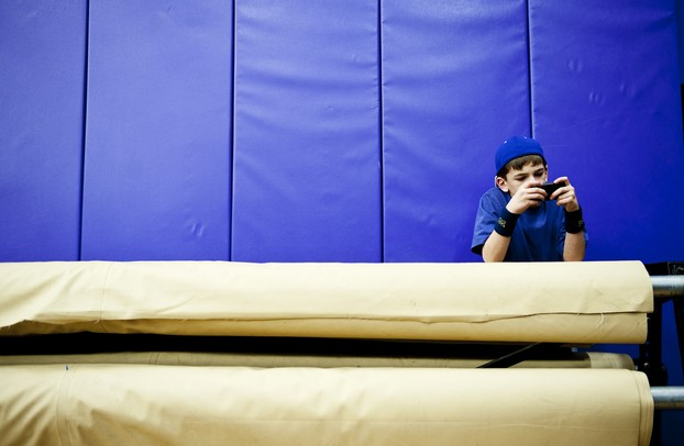 Twelve-year-old Ben Kunec plays a video game while his brother plays in the Pioneer junior varsity game on Friday, Jan. 18. Daniel Brenner I AnnArbor.com
