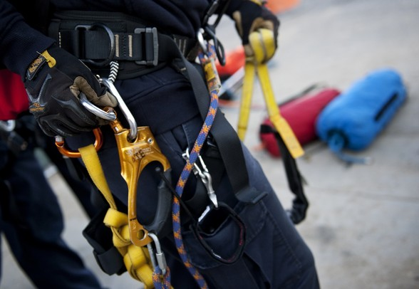 An emergency rescue technician checks ropes and carabiners on his harness before simulating a training exercise at the construction site of First and Washington streets on Sunday. Daniel Brenner I AnnArbor.com