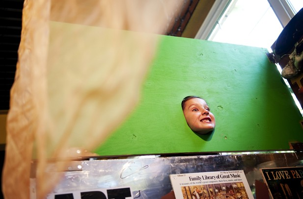 Ann Arbor resident Grace Heard, 6, sticks her head through the Heidelberg Project mobile video booth at the last Shadow Art Fair at the Corner Brewery in Ypsilanti on Saturday, July 20. Daniel Brenner I AnnArbor.com