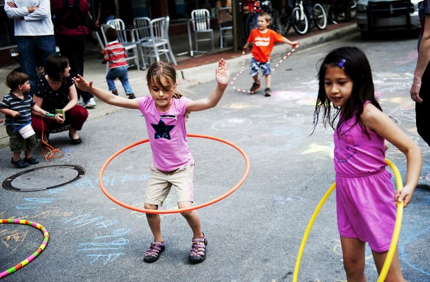 Ann Arbor residents Jane Slocum, 6, and Maya Max, 7, play with Hula-Hoops on top of chalk drawings during the Taste of Ann Arbor on Sunday, June 2. Daniel Brenner I AnnArbor.com