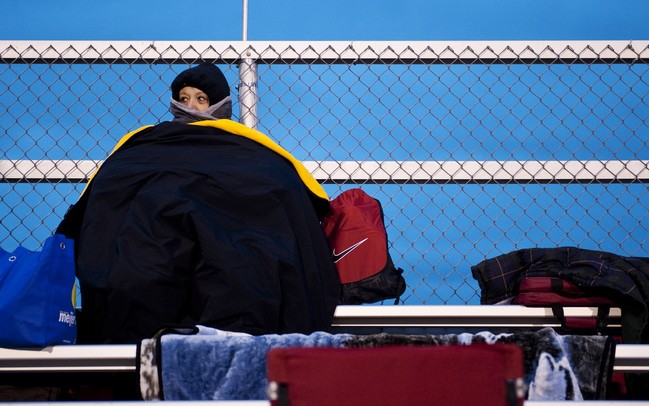 Milan High School supporter Connie Majeske tries to stay warm before the game against Tecumseh on Friday. Daniel Brenner I AnnArbor.com