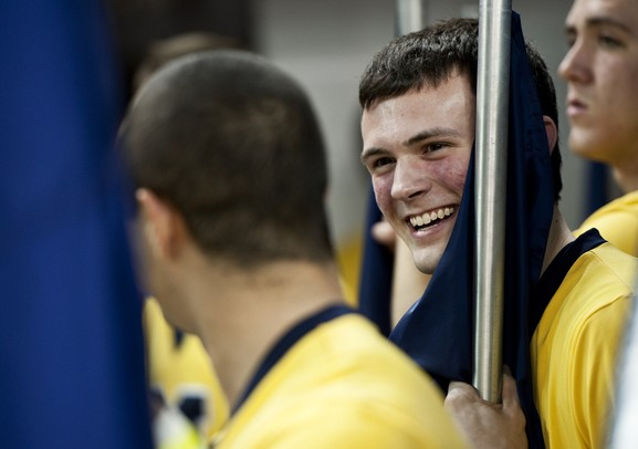 Michigan junior cheerleader Chris Fraga smiles while holding a flag before the game against Western Michigan on Tuesday. Daniel Brenner I AnnArbor.com